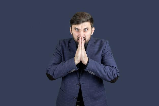 Ein mann mit bart und blauem anzug faltete die hände, die handflächen einander zugewandt