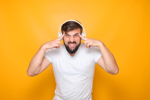 Ein mann mit bart und kopfhörer hält seine finger an seine schläfe und hört musik.