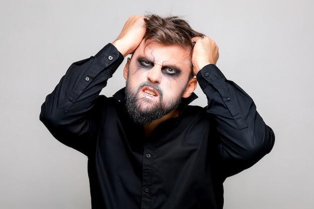 Ein mann mit bart und make-up für halloween packte seine haare mit den händen