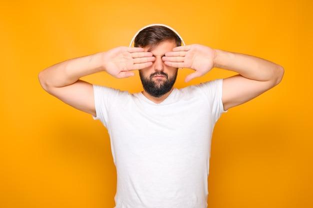 Ein mann mit bart und weißen kopfhörern schließt die augen mit den handflächen.