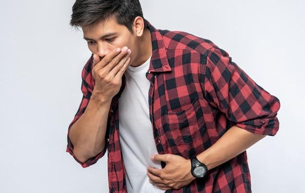 Ein mann mit bauchschmerzen steh deine hände auf deinen bauch und bedecke deinen mund.