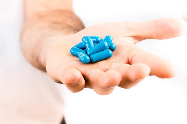 Ein mann mit blauen medikamenten- oder nahrungsergänzungskapseln in der hand mit weißem hintergrund