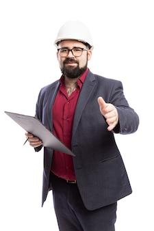 Ein mann mit brille, bart in weißem bauhelm und tablette in der hand. in einem formellen anzug gekleidet. isoliert auf einer weißen wand. vertikale.