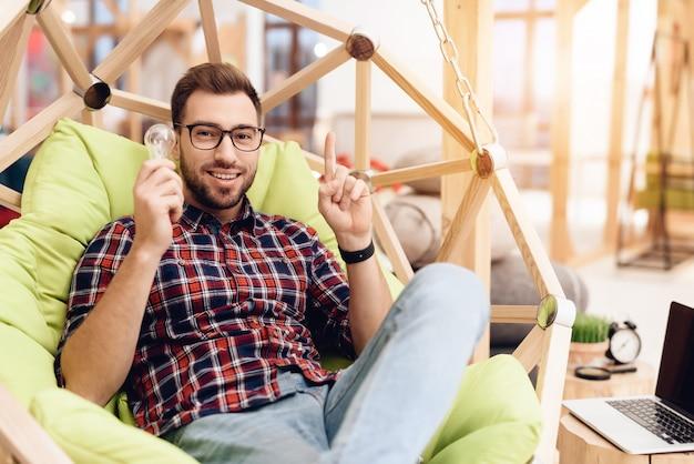 Ein mann mit brille sitzt auf einem stuhl und hält eine glühbirne.
