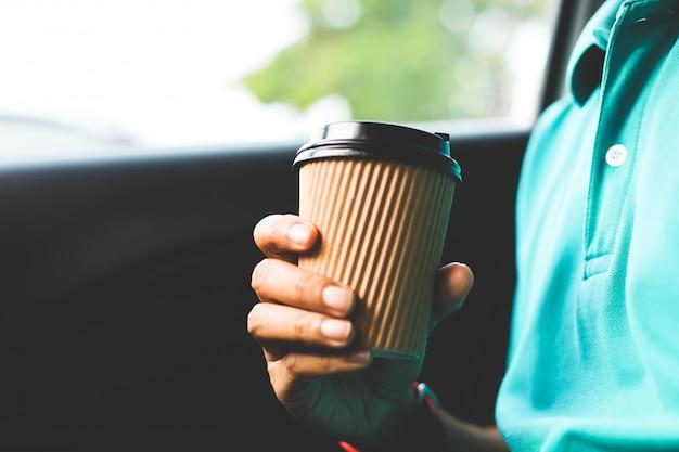 Ein mann mit dem grünen hemd, das einen tasse kaffee im auto hält.