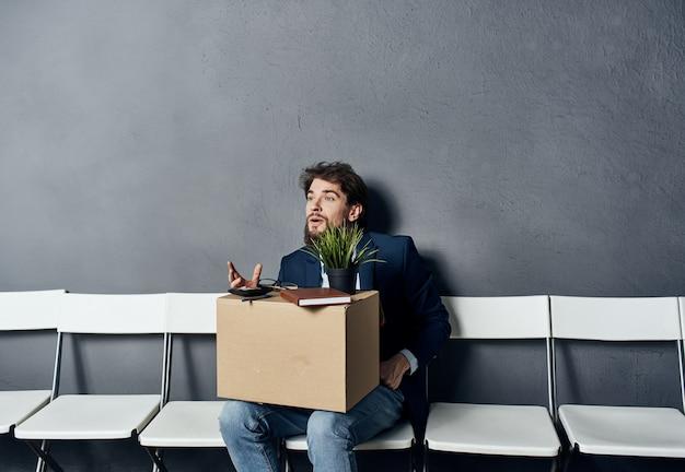 Ein mann mit dingen in einer kiste sitzt auf einem stuhl und wartet auf unzufriedenheit