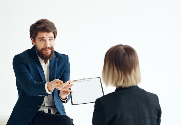 Ein mann mit dokumenten im anzug und eine frau für ein vorstellungsgespräch