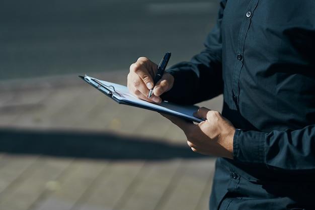 Ein mann mit dokumenten in den händen in ihren schwarzen hemden auf der straße mit einem stift in der hand.