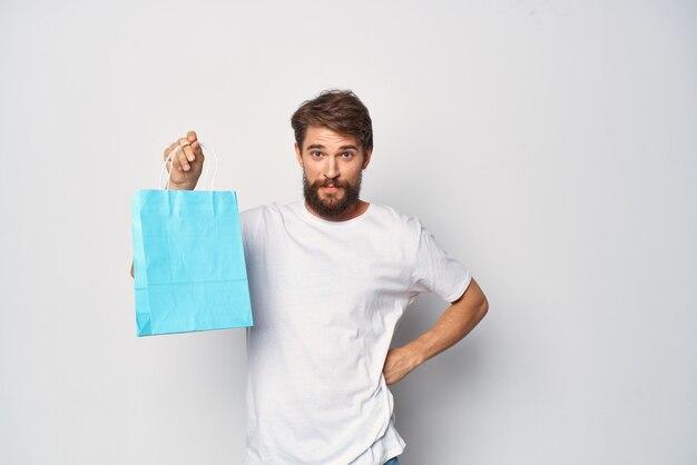 Ein mann mit einem blauen päckchen in der hand, der modekleidung einkauft