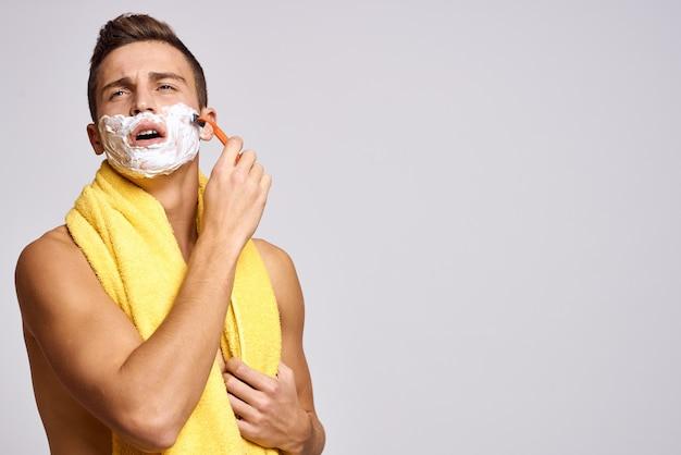 Ein mann mit einem gelben handtuch auf den schultern und einer weißen, rasiermesserscharfen, sauberen haut.
