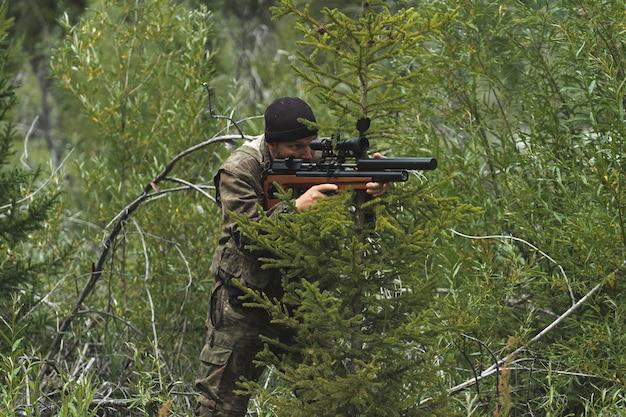 Ein mann mit einem gewehr sitzt in einem hinterhalt. der scharfschütze bereitet sich zum schießen vor.