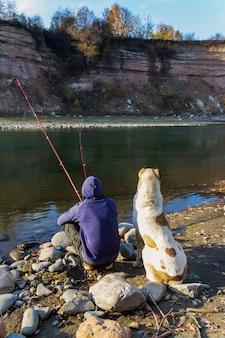 Ein mann mit einem großen zentralasiatischen schäferhund, der an einem herbsttag im fluss fischt