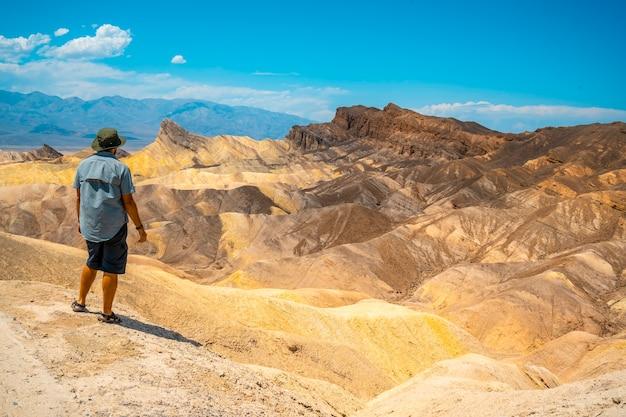 Ein mann mit einem grünen hemd auf dem schönen standpunkt von zabriskre point, kalifornien. vereinigte staaten