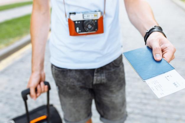 Ein mann mit einem koffer und einer kamera, der einen pass und tickets in nahaufnahme hält