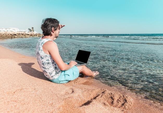 Ein mann mit einem laptop im sand schaut in die ferne und arbeitet als freiberufler