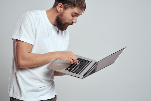 Ein mann mit einem laptop in seinen händen auf einem hellen raum in einem weißen t-shirt emotionen lichtraum beschnitten ansicht modell porträt neue technologien.