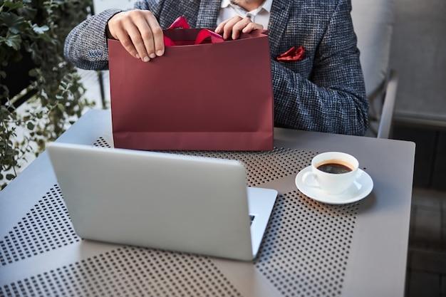 Ein mann mit einem laptop öffnet eine rote geschenktüte, während er in einem café sitzt