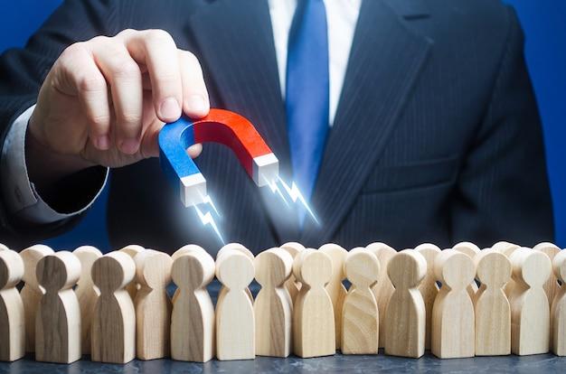 Ein mann mit einem magneten ist auf der suche nach kandidaten für die arbeit in der menge.