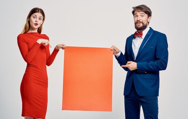 Ein mann mit einem roten blatt papier in den händen und einer frau in einem kleid mocap poster werbung.