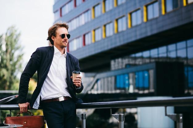 Ein mann mit einem schönen bart steht auf der straße in einem blauen anzug und einer orangefarbenen ledertasche, während er seinen kaffee trinkt