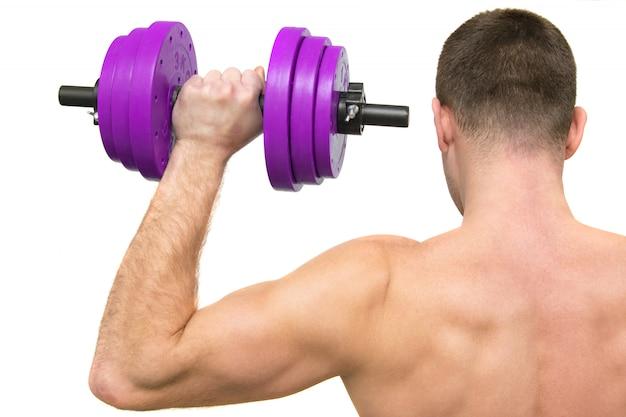 Ein mann mit einem schönen körper beschäftigt sich mit fitness. der blick von hinten. isoliert