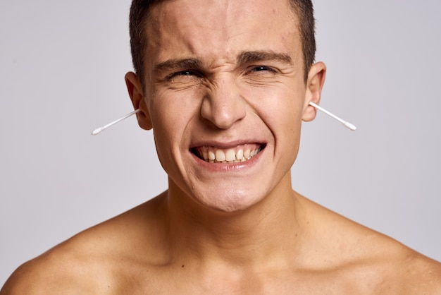 Ein mann mit einem wattestäbchen auf einem hellen raum und einem nackten oberkörper schnitt eine klare hautansicht ab