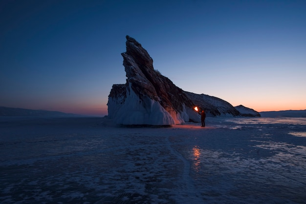 Ein mann mit einer brennenden fackel steht in der nähe von ogoy island bei frühem sonnenaufgang.