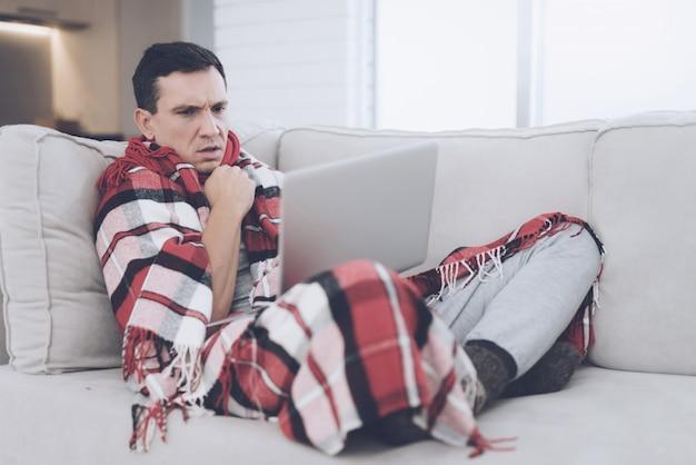 Ein mann mit einer erkältung sitzt auf der couch.