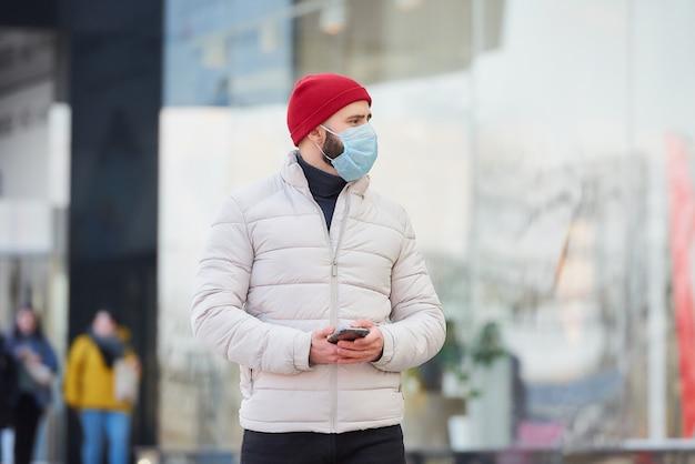 Ein mann mit einer gesichtsmaske im gesicht mit einem smartphone im zentrum der stadt.