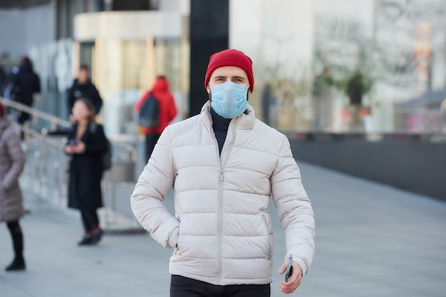 Ein mann mit einer gesichtsmaske im gesicht wegen der pandemie auf der straße