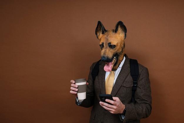Ein mann mit einer latex-hundekopfmaske und einem rucksack, der ein smartphone handhabt und eine tasse kaffee in der hand hält
