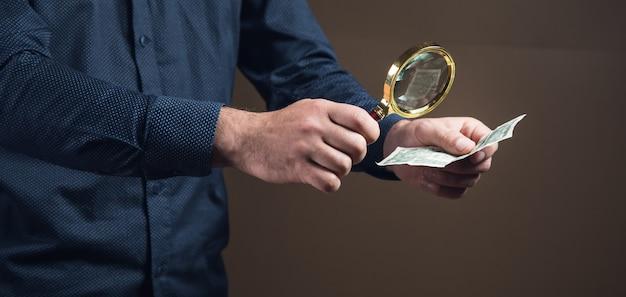 Ein mann mit einer lupe betrachtet geld auf einer braunen oberfläche