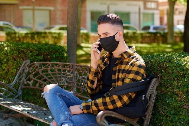 Ein mann mit einer maske sitzt auf einer bank, während er mit seinem handy anruft