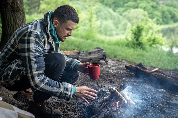 Ein mann mit einer tasse wärmenden getränks wärmt sich am feuer im wald.