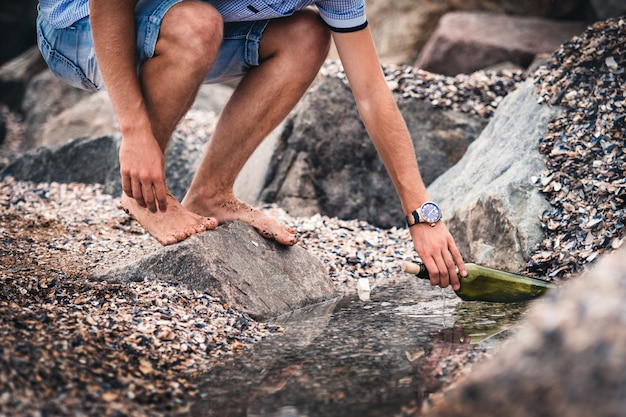 Ein mann mit einer uhr auf dem zeiger stellt eine flasche mit einer nachricht wasser auf das meer