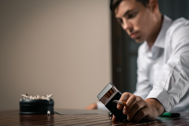 Ein mann mit einer zigarette und einer packung in der hand posiert am tisch, auf dem ein bild der fluorographie liegt