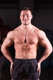 Ein mann mit gemischten rassen trainiert an einer schmetterlingsmaschine im fitnessstudio.