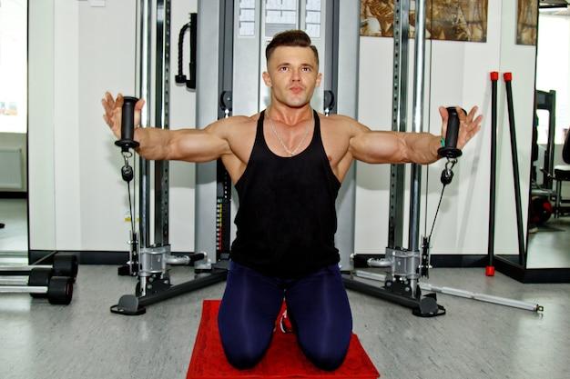 Ein mann mit großen muskeln beschäftigt sich im fitnessstudio mit gewichtheben. ein aufgepumpter athlet treibt sport auf schwergewichtssimulatoren. sportliche übungen.