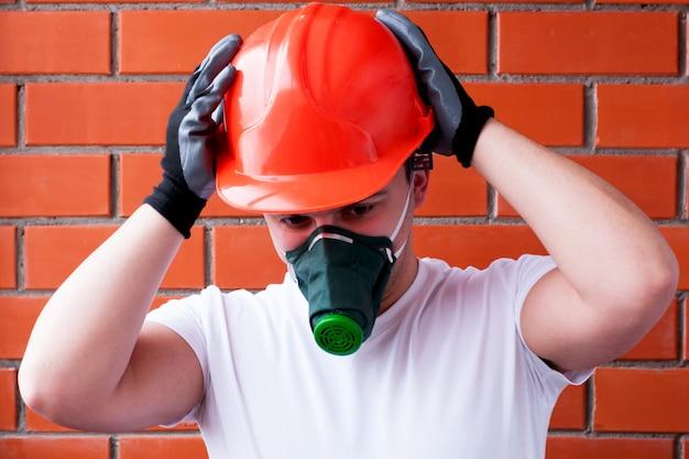 Ein mann mit helm und atemschutzmaske bemalt eine betondecke