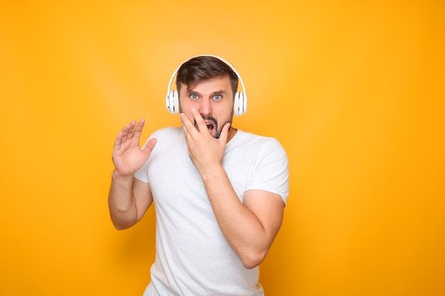 Ein mann mit kopfhörern, der musik hört, greift sich den mund und demonstriert entsetzen.
