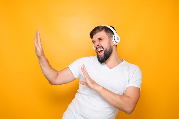 Ein mann mit kopfhörern hört musik und schreit.