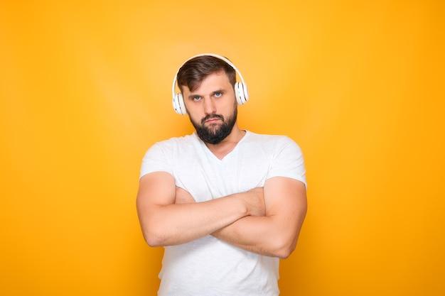 Ein mann mit kopfhörern verschränkte die arme vor der brust und hört musik über kopfhörer.