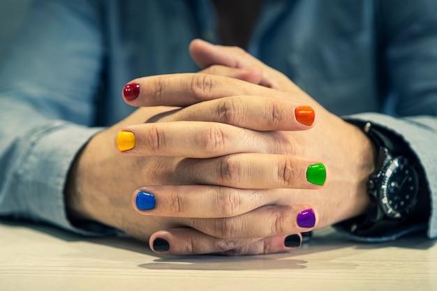 Ein mann mit lackierten nägeln. design von männlichen nägeln. männer maniküre. die nägel sind in der farbe des regenbogens lackiert.