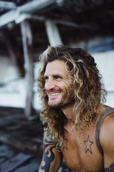 Ein mann mit langen lockigen haaren in einem fischerort. fischer auf dem ozean