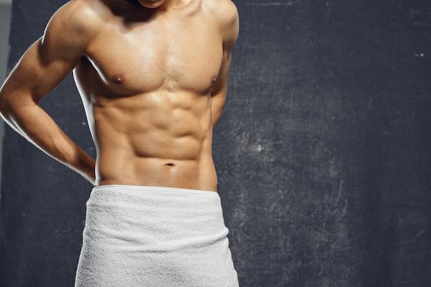 Ein mann mit nacktem, aufgepumptem oberkörper bedeckt sich mit einem fitness-bodybuilderhandtuch. foto in hoher qualität