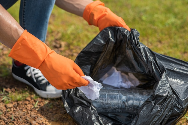 Ein mann mit orangefarbenen handschuhen sammelt müll in einer schwarzen tasche.