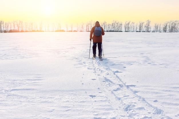 Ein mann mit rucksack auf skiern im schneebedeckten feld. freiheit, abenteuerkonzept. einsamkeit.