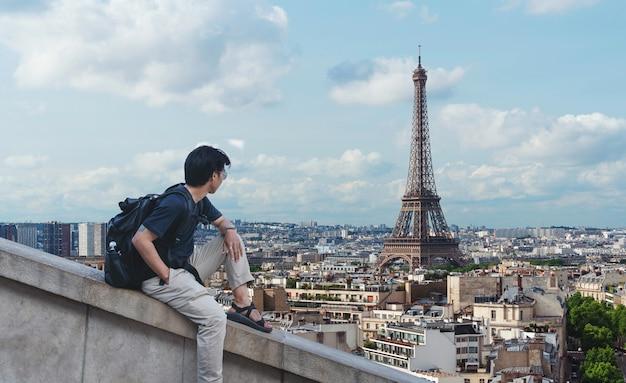 Ein mann mit rucksack, der eiffelturm, berühmtes wahrzeichen und reiseziel in paris, frankreich betrachtet