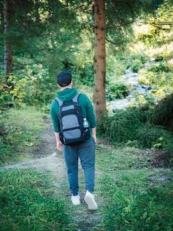 Ein mann mit rucksack geht im herbstwald spazieren. alleine auf herbstlichen waldwegen wandern. reisekonzept.