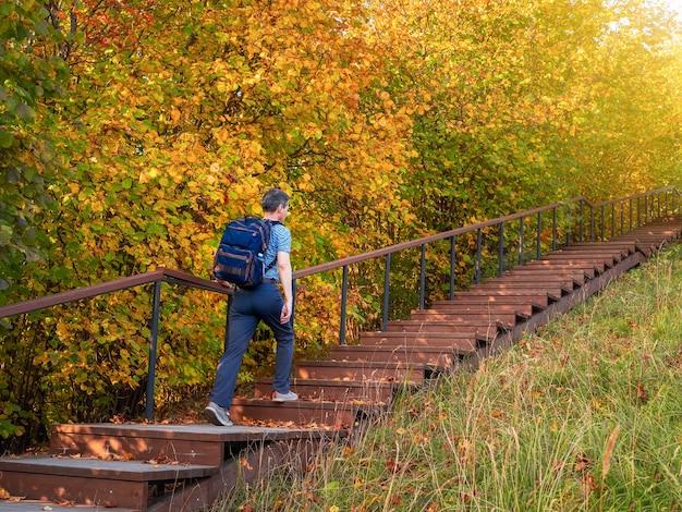 Ein mann mit rucksack steigt im herbst auf den öko-trail